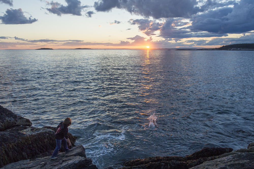 Nathan Stephansky '17 skips a rock into the Atlantic at sunset.