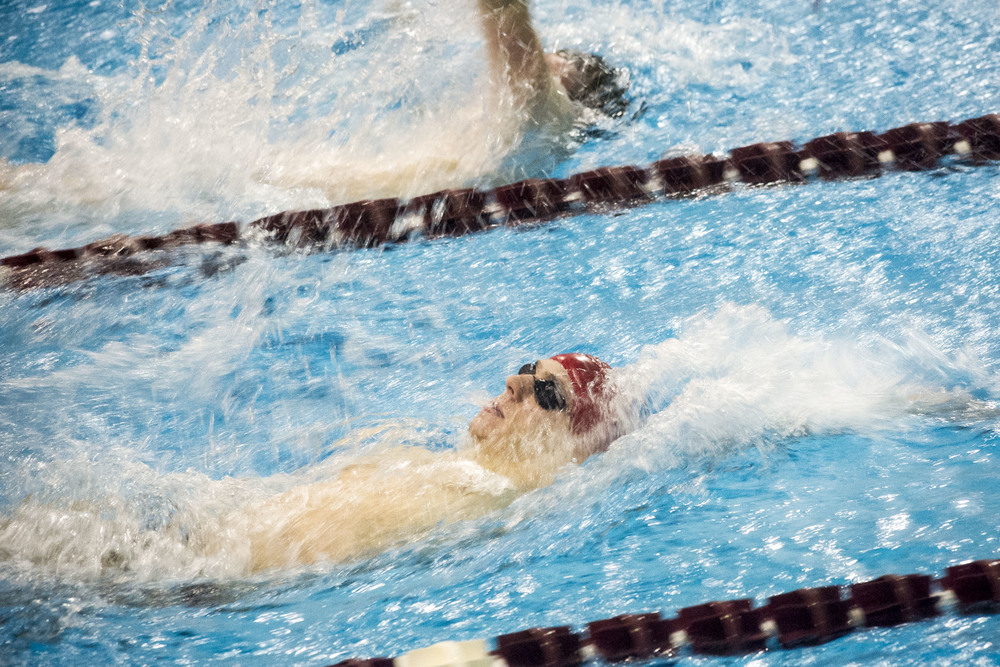 Zachary Collester '19 approaches the finish of the 100 backstroke against Trinity at Tarbell Pool.