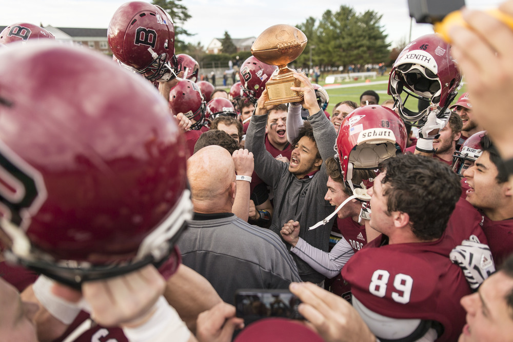 Shaun Carroll '16 holds up the CBB (Colby-Bates-Bowdoin) Championship trophy his teammates fought to retain after Bates' 31-0 win over Bowdoin College.