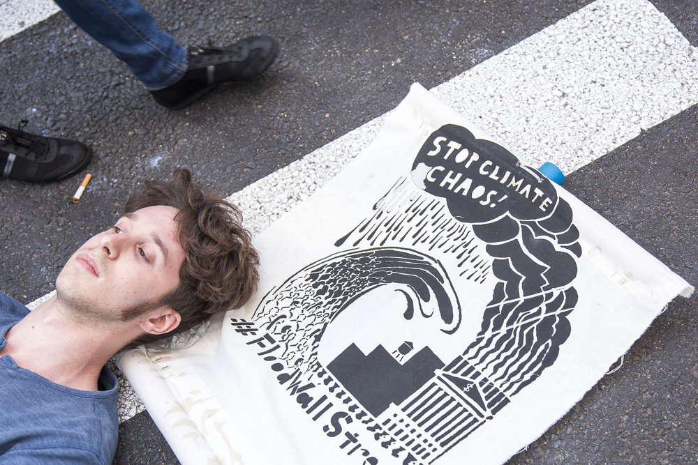 A protestor rests his head on top of a poster on Broadway where it intersects Wall Street.