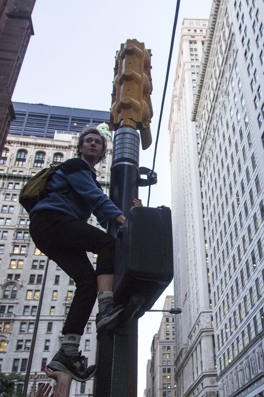 Against the wishes of the NYPD, a protestor scales a traffic signal for a better view.