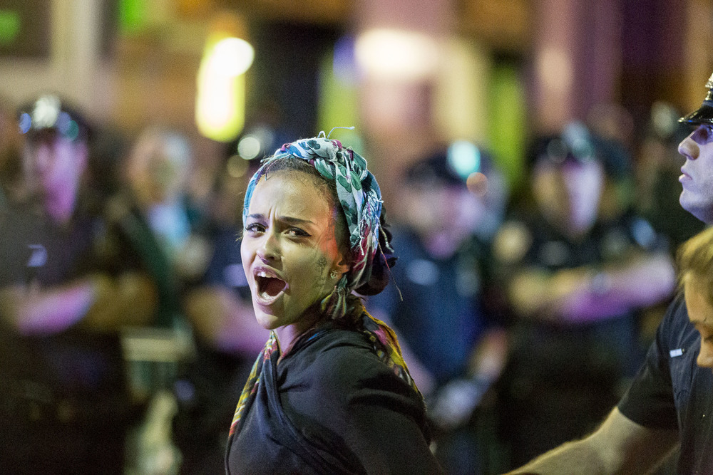 A protester responds to congratulations from friends in the crowd as she is arrested.
