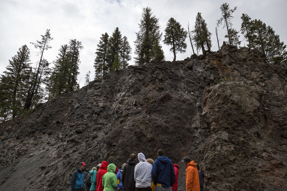 Donning colorful rain jackets, the class huddles next to the road in Firehole Canyon inside Yellowstone National Park.