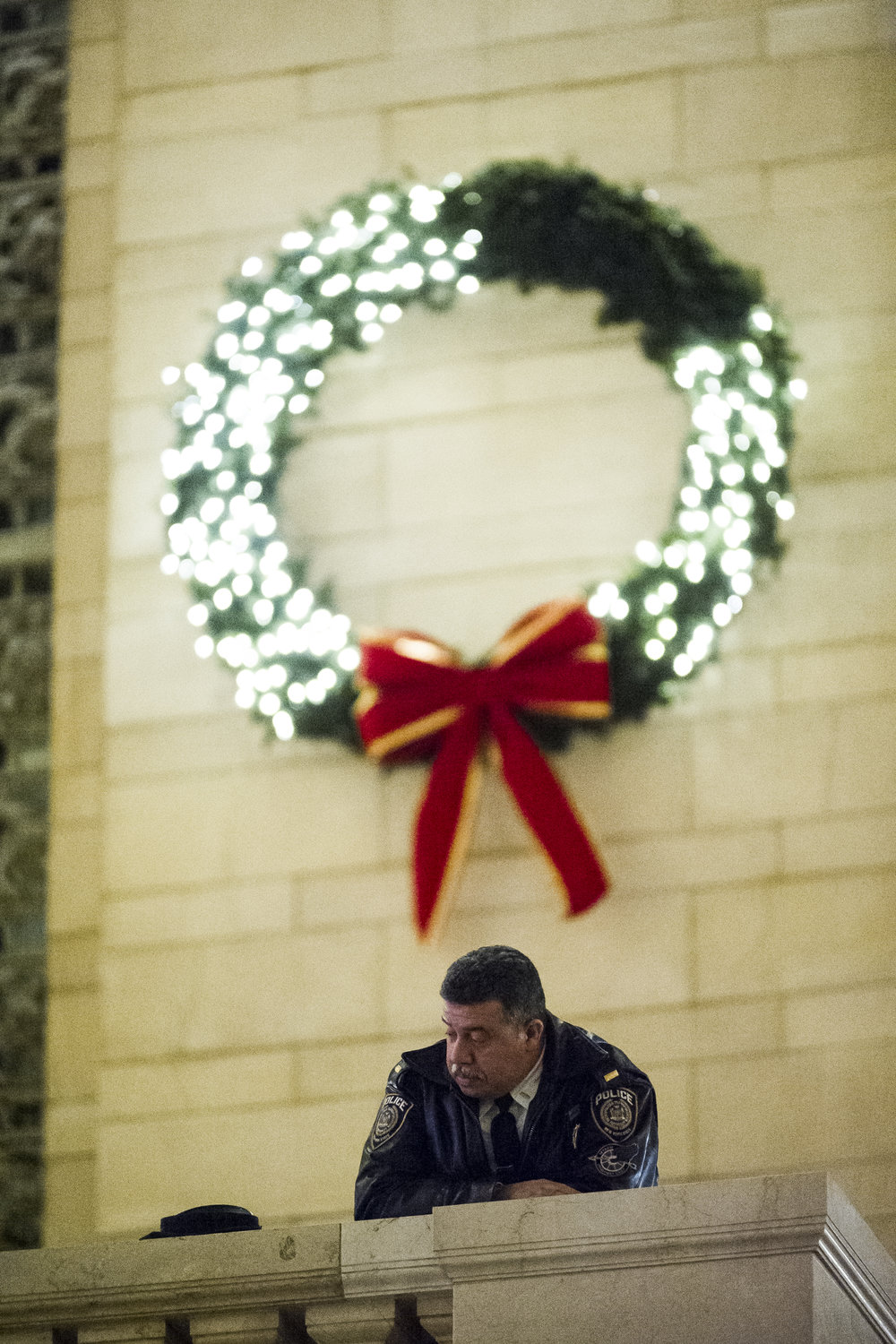 "An NYPD officer looks on from above as demonstrators take part in a ""die-in"" in the main atrium of Grand Central Station. Weeks of protest followed a Staten Island grand jury's decision on December 3rd 2014 not to indict Officer Daniel Pantaleo in the killing of Eric Garner."