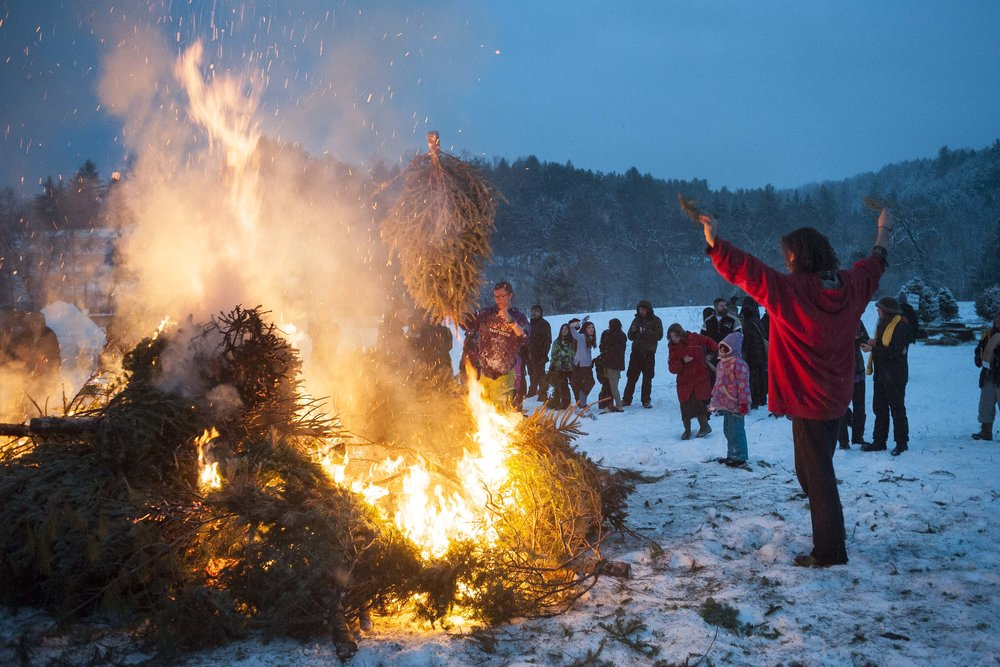 Participants gather around a bonfire during the conclusion of Ice on Fire, a winter festival held at the North Branch Nature center in Montpelier on Sunday, February 4th 2018.