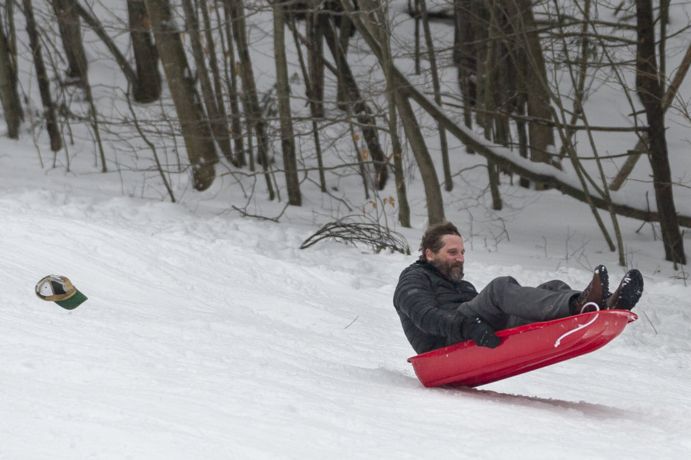 Patrick Hayes of Wadmalaw Island, South Carolina, loses his hat while making the most of his northern visit sledding at Hubbard Park in Montpelier on Sunday, February 11th 2018.