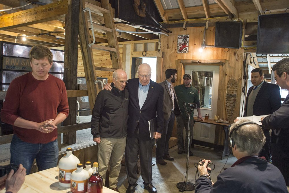 "Representative Peter Welch (D-VT) and Senator Patrick Leahy (D-VT) share a moment on May 1st, 2018 after the completion of a press conference at Morse Farms in East Montpelier to highlight opposition to an FDA proposal to require an ""added sugar"" label on pure maple syrup."