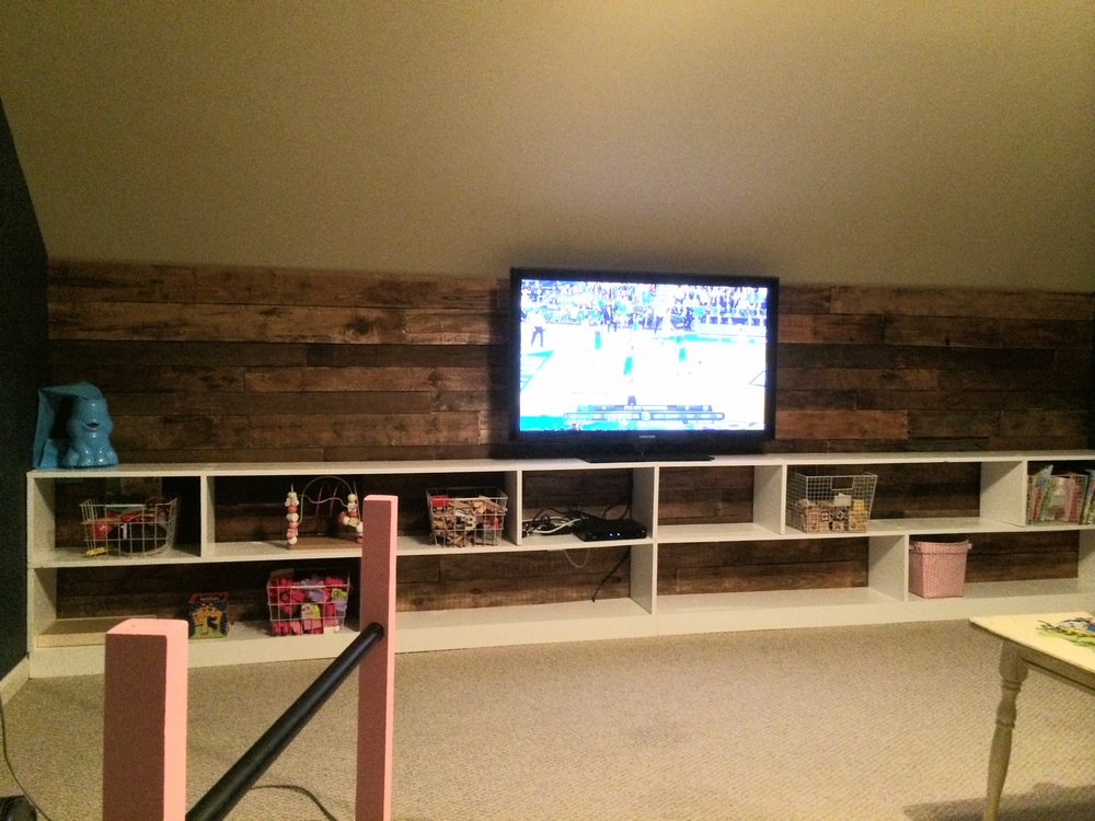 Finished product with some toys and baskets on the shelves...basketball on the TV!