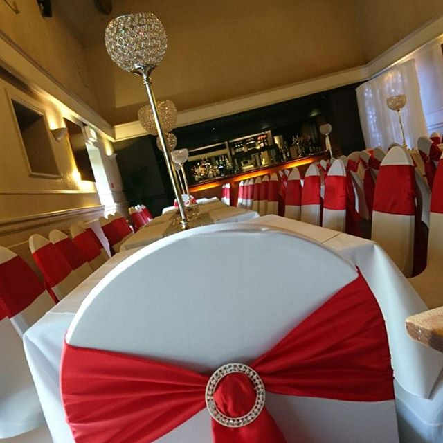 Red taffeta sashes with diamanté sliders on white chair covers with our gorgeous crystal globe centrepieces and silver sequin runners and table cloths for Sharon & Kevin's wedding party today! #sparkle #weddingbling #wedmin #venuedecor #eventstyling #venuedresser #chaircovers #weddingbants #getfunked