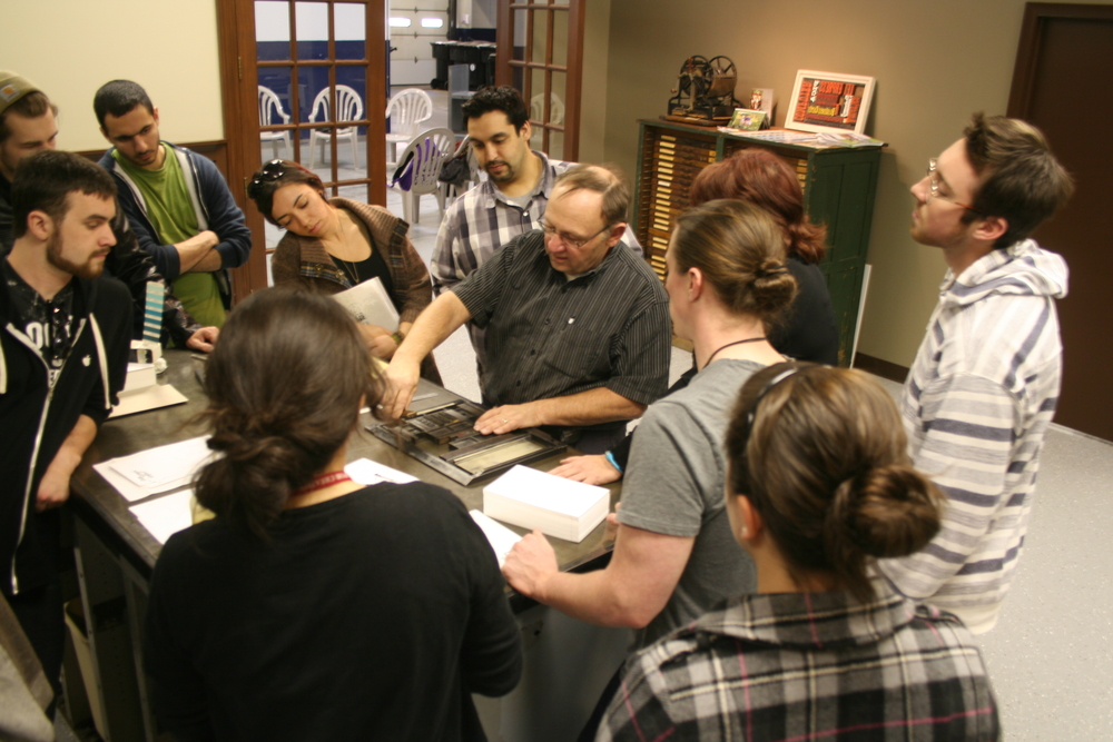 A visiting class from College for Creative Studies watches a demonstration of letterpress printing during a field trip to the studio.