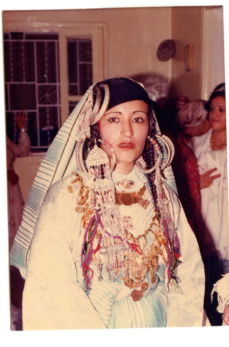My mother in traditional Amazigh (Berber) dress. You might even notice my aunt's hand in the background signing Peace out!