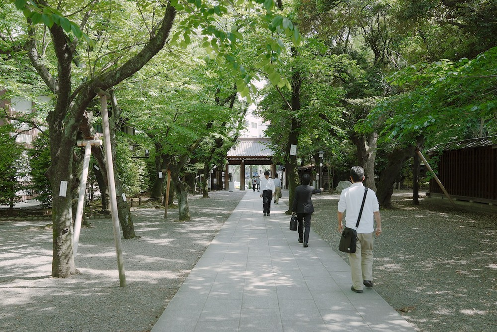 Business men leaving after a moment of serenity at Yasukuni shrine.