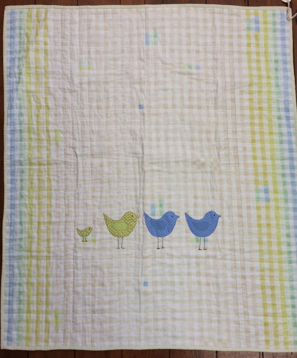 Birds appliquéd onto a whole cloth cot quilt.