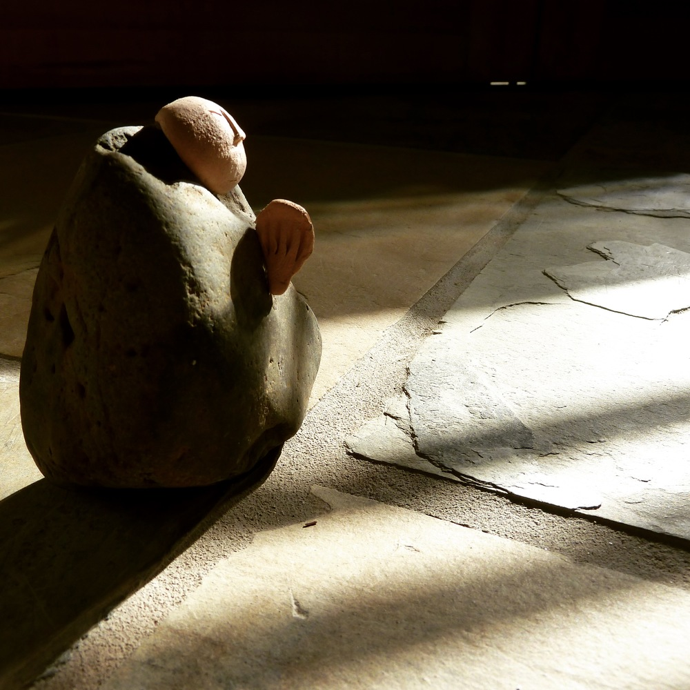 Three inch tall stone monk, praying in the morning light.