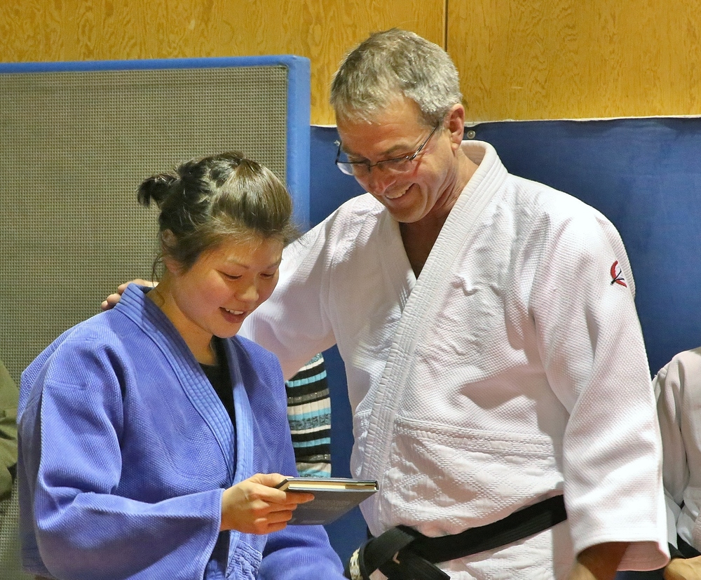 Adelphi receiving her black belt from Ken Frail