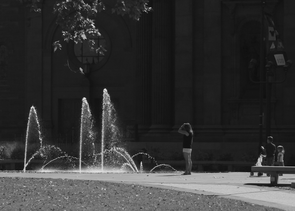 a woman enjoys a fountain near Logan Square