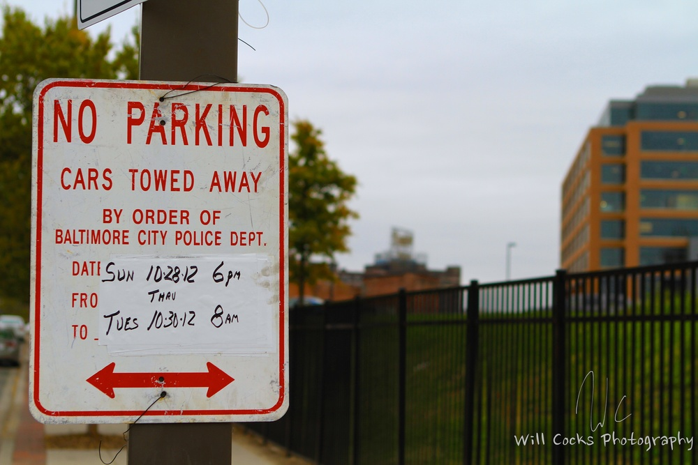 A No Parking Sign on Caroline St in Baltimore, MD, With the Domino Sugar Factory in the background.