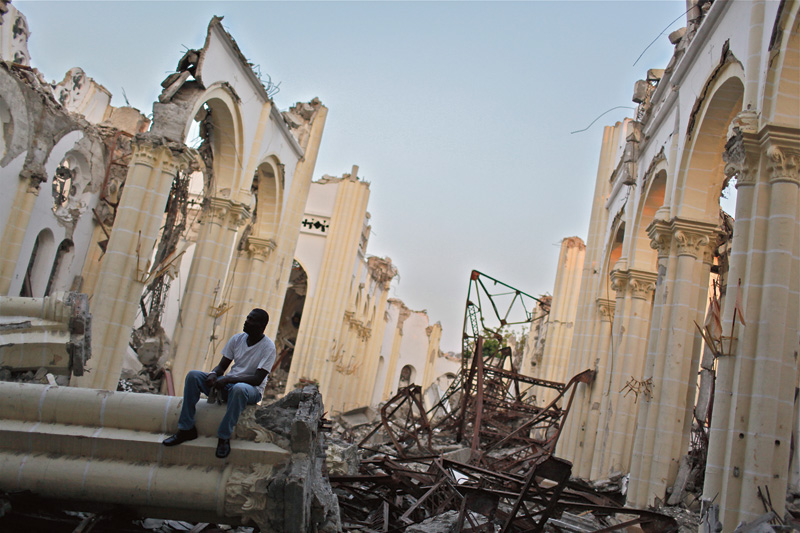 A man sits in the ruins of the destroyed Cathedrale Notre-Dame de L'Assomption in Port-au-Prince