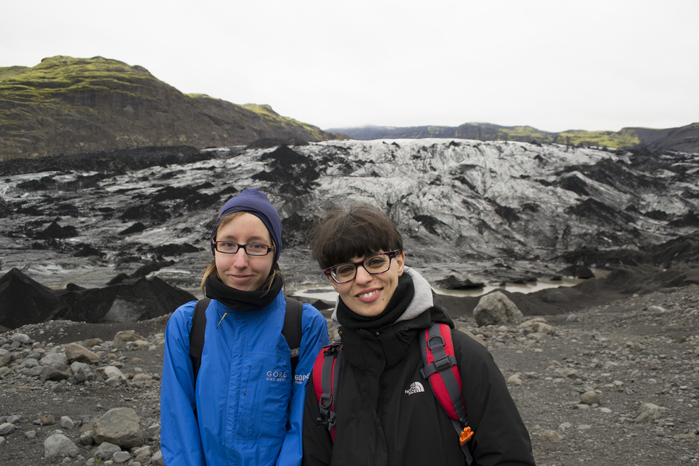 Maike Plenzke and Gloria Pizzilli stand in front of an incredible ash-covered glacier.