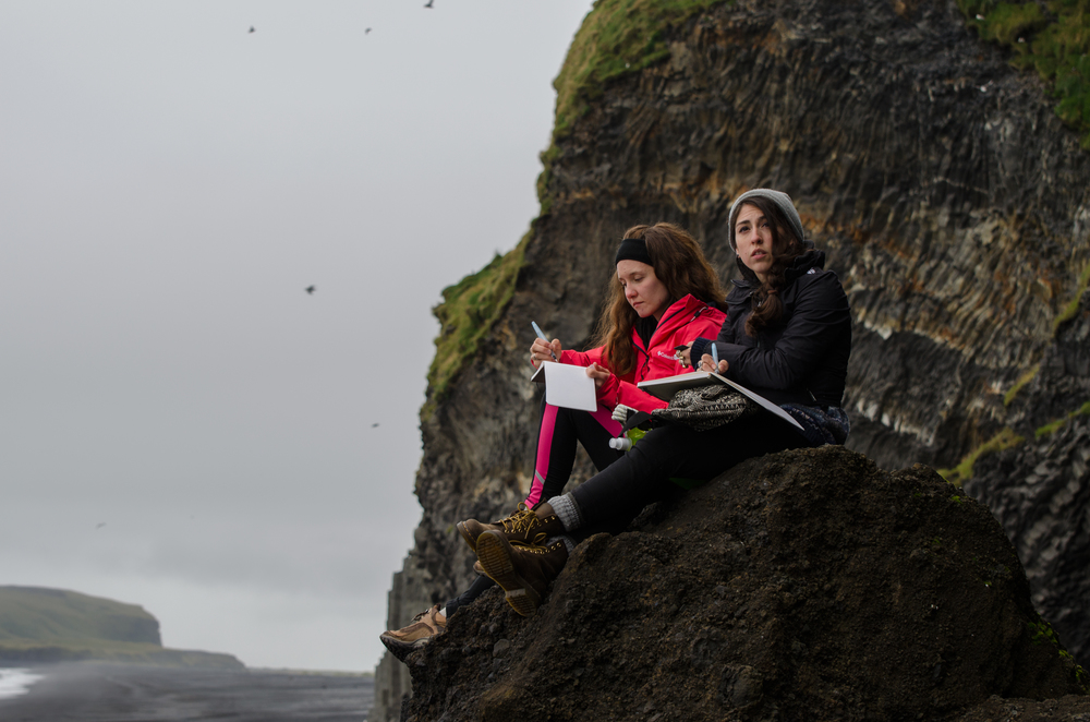 Jenny Bookler and Lindsay Nohl sketch near the black basalt beaches of Reynisdrangar