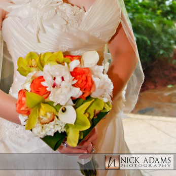 A tropical bouquet of Orchids, Calla Lillies and Roses in white, green and orange.