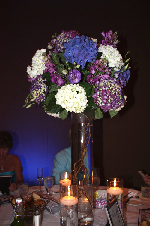 Tall purple centerpiece featuring hydrangea framed by floating candles.