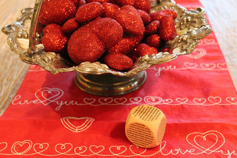 A silver basket filled with glittering hearts on a red table runner.