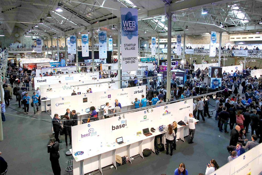 Web Summit main hall, with hanging vinyl banners, and 250x numbered exhibitor boards, with logo, country, and symbols indicating participation in various programmes at the Web Summit.