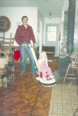 My sister Natalie riding a carpet cleaning buffer with my dad.