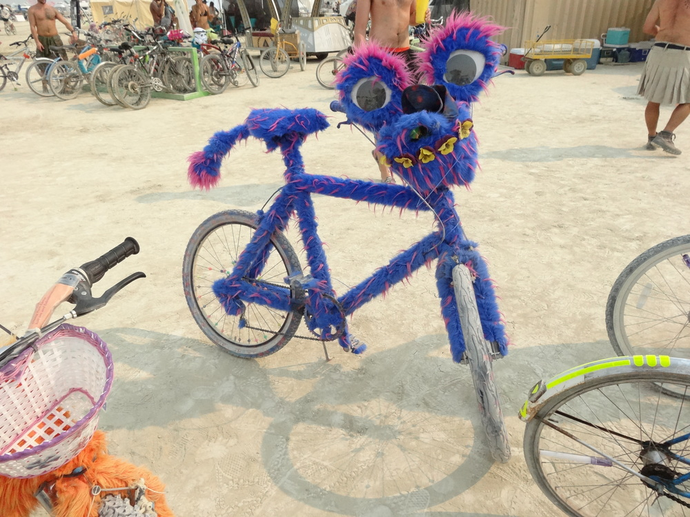 One of the many wildly-decorated bikes at Burning Man. EL wire wrapped around the blue fur outlined the bike's tubes in glowing neon blue spirals at night.  Most de-commodification is accomplished by adding extravagant decoration. Vibrant fur is a classic Burner favorite.