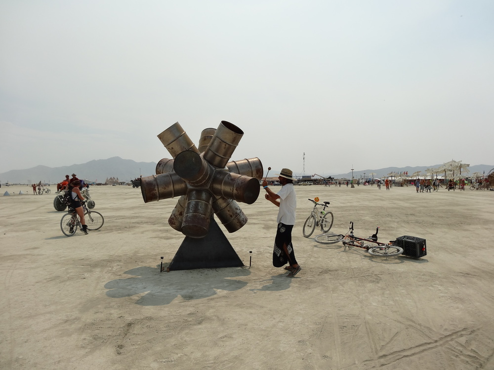 A burner plays a cluster of steel drums on a rotating base. Most installation art here involves viewer interaction.