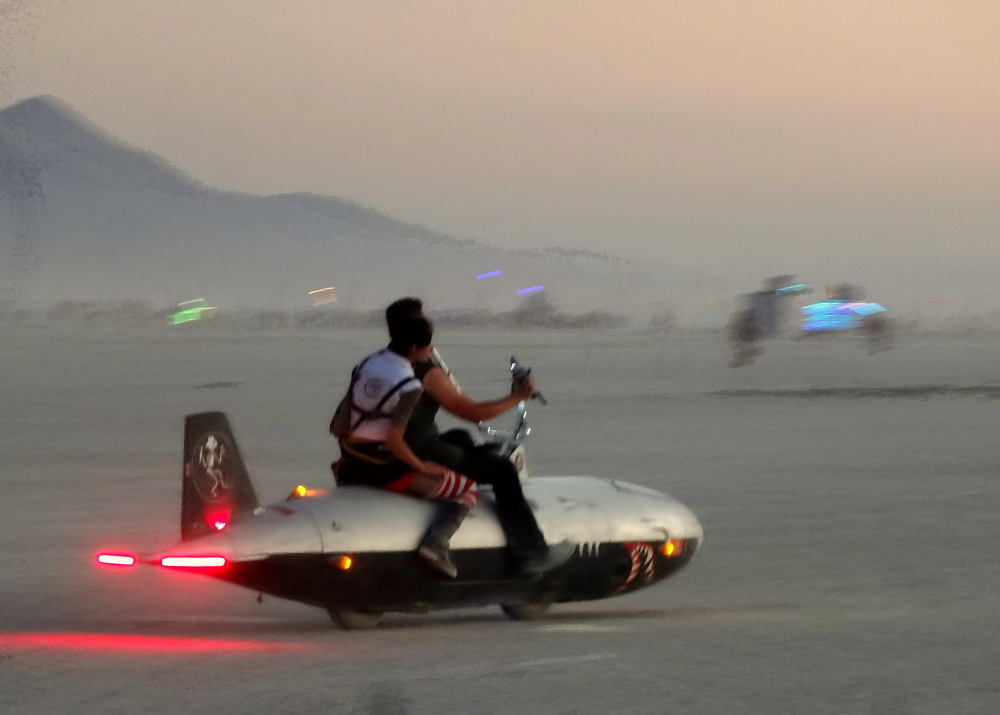 A two-person mutant vehicle cruises the playa at dusk.