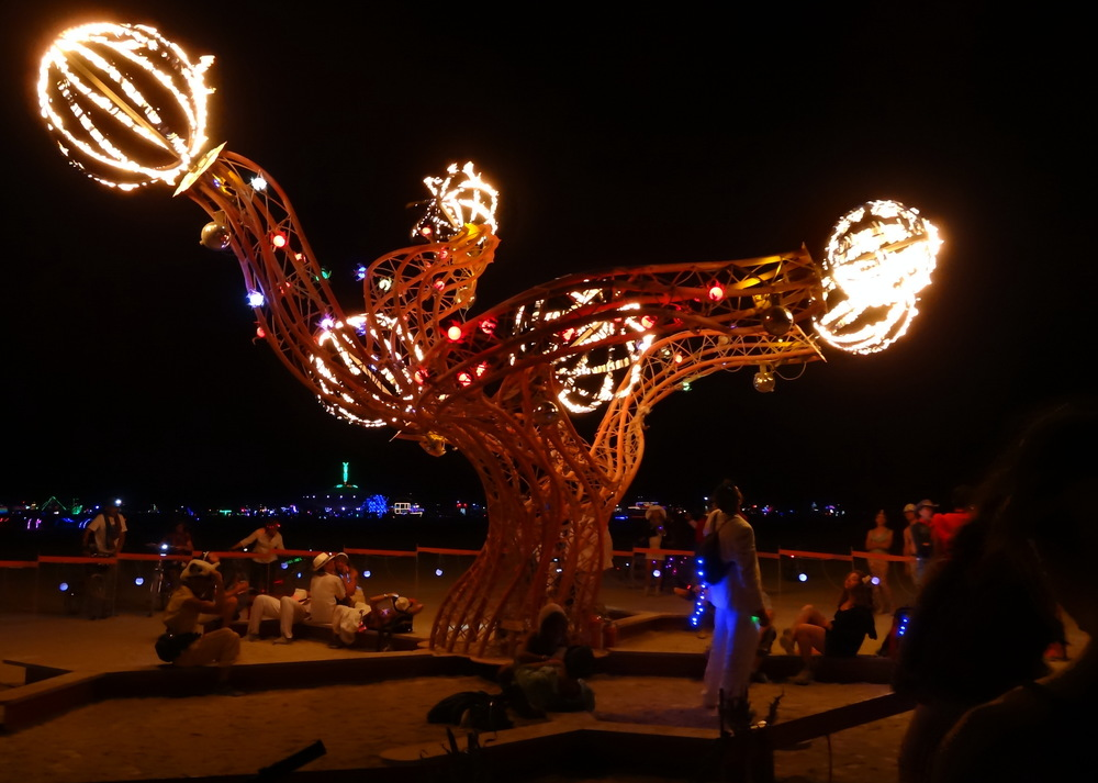 One of the many installations lit up by fire at night. The Man can be seen in the distance, lit up in green light.