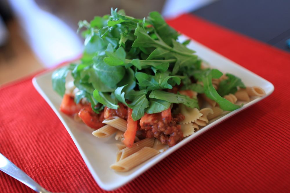Traditional Bolognese Pasta Topped with Arugula