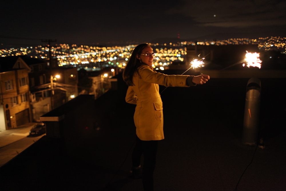 nicole celebrates new years on the rooftop,  with the lights of bayview as her backdrop.