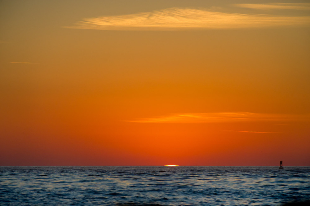 The first sliver of sun begins to rise over the Atlantic Ocean.
