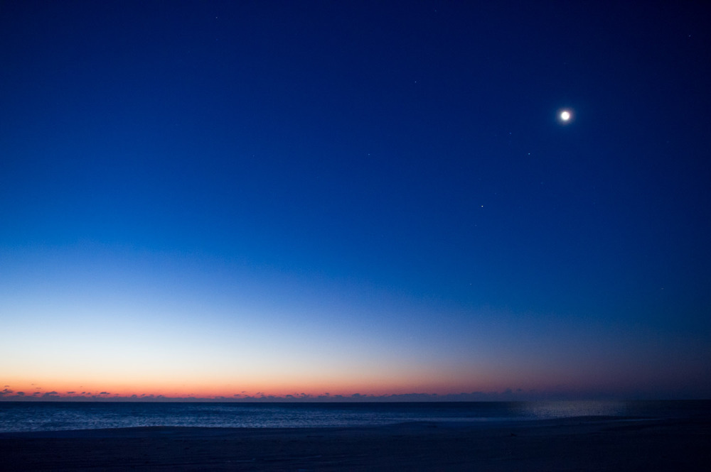 Standing on the beach you can see the moon and stars as the sun begins to light up the horizon.