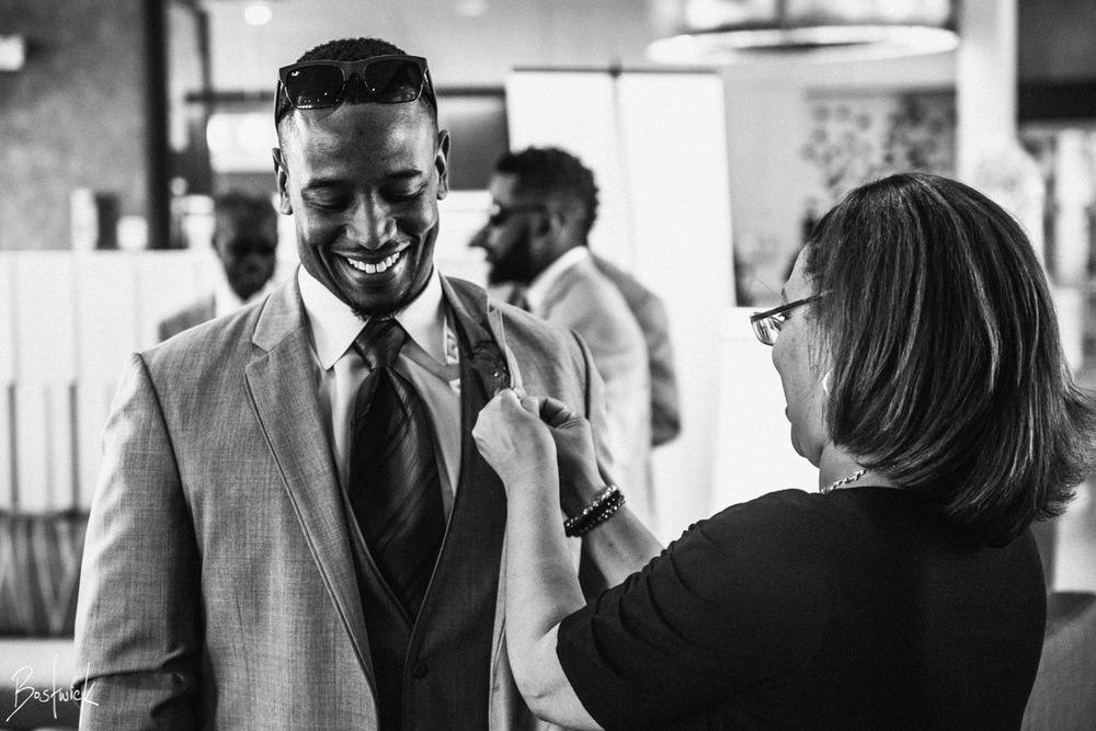 Chief Event Planner Randi Martin pinning the boutonniere on a groomsman. Photo by Daniel Bostwick Photography
