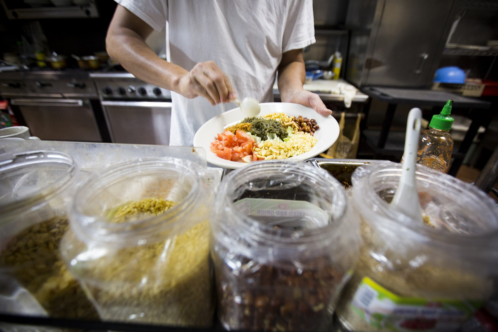 Owner and top chef of Yoma restaurant Sai Kyaw preparing tea salad in the kitchen.