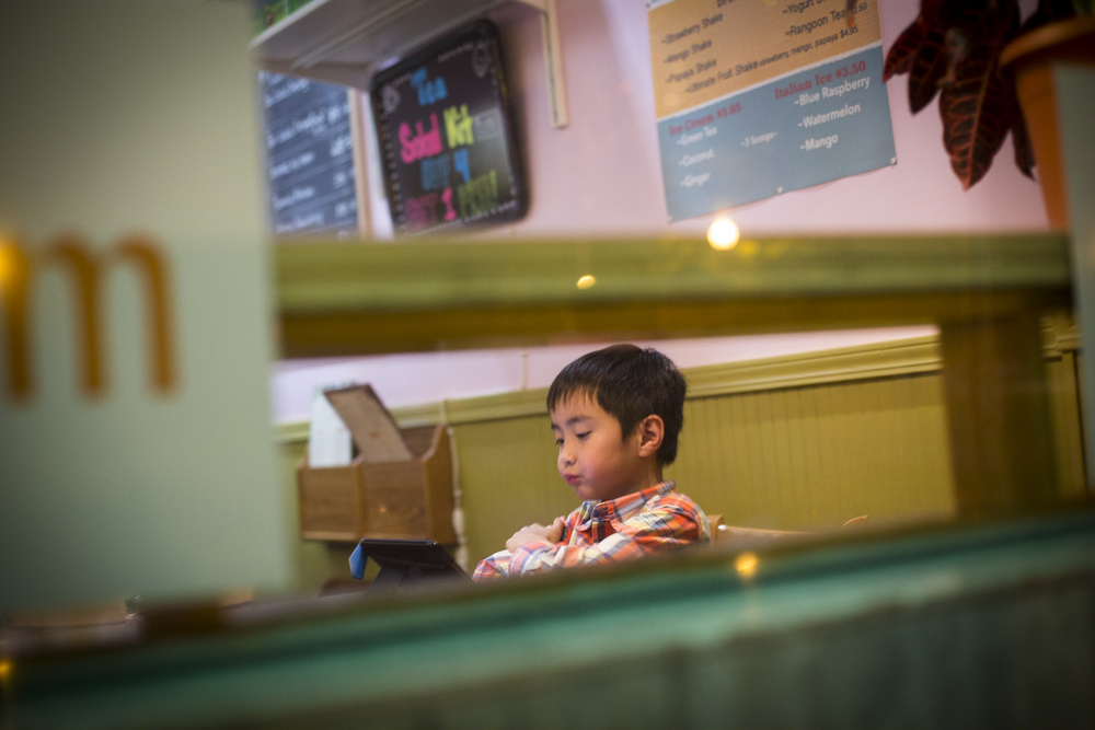 Henry Kyaw, 7. When the restaurant is less busy, Henry, the son of the owner of Yoma, can take the seat in the restaurant and play games on his tablet. By Ann Wang