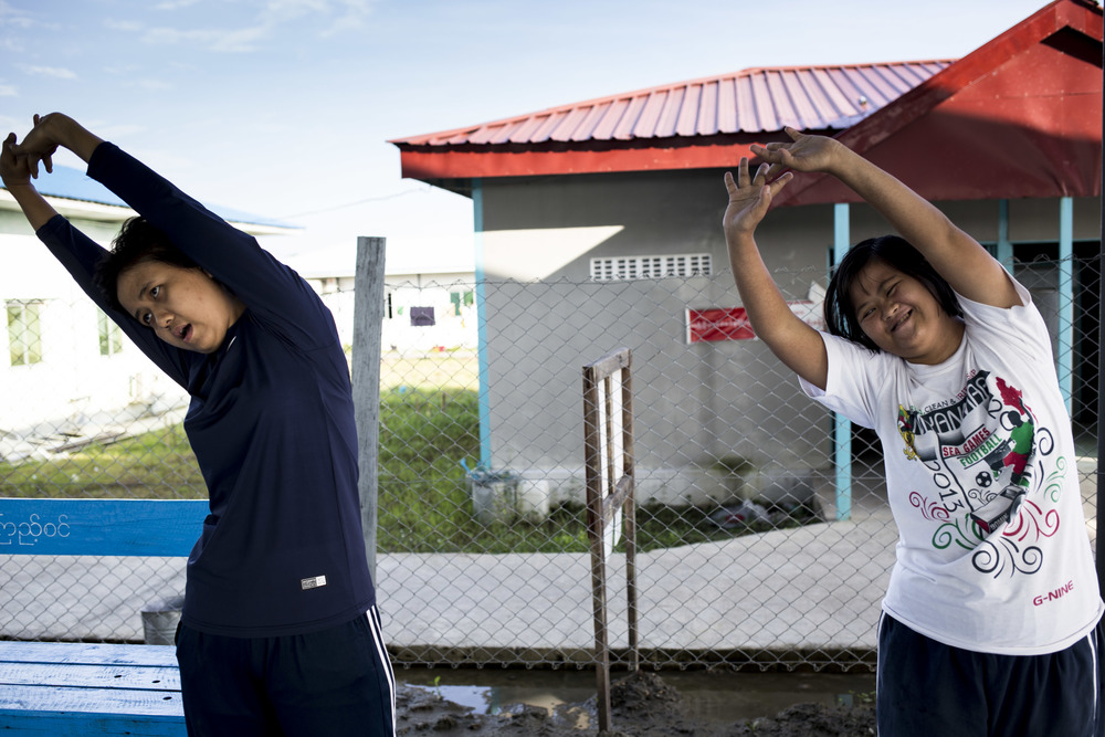 Theint theint Thu, 19 (left) goes to swimming training four times per week at the North Dagon sports stadium for the disabled. According to her family, Theint Theint has lost a lot of weight since started the swimming class four months ago, she is healthier and happier, because she has made friends with other down syndrome people at the swimming pool. Photo by Ann Wang