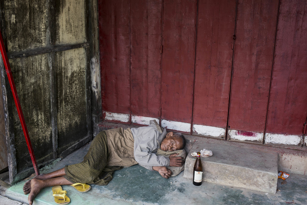 A drunk man is seen in downtown Yangon. The bottle in front of him is rice wine from Myanmar, which contents 40% alcohol and can be purchased under 1000 kyet (1 usd). Photo by Ann Wang