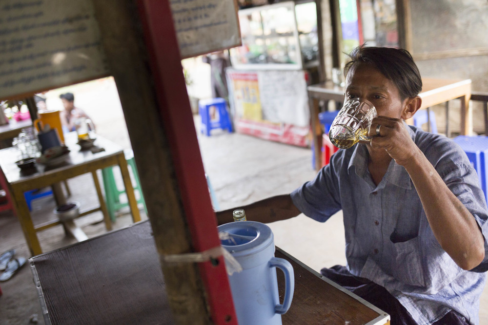 """I drink at least five bottles of whisky everyday,""said the drunk man at a local street side bar in South Dagon. Photo by Ann Wang"