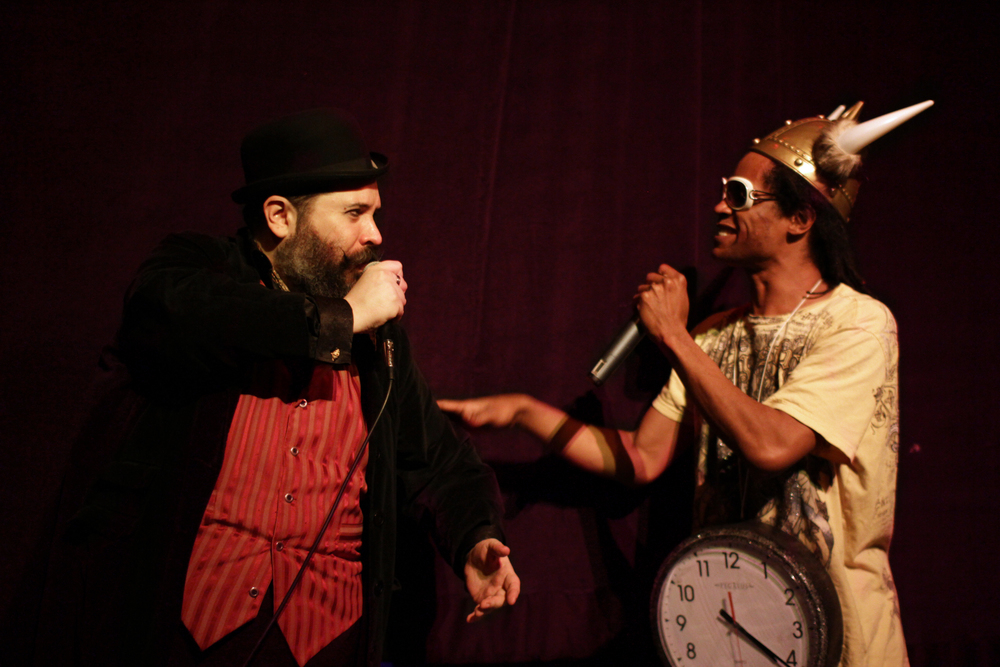 David Slone  as Charles Darwin, and  Kay Mazing  as Flava Flav.   ©CBMarney