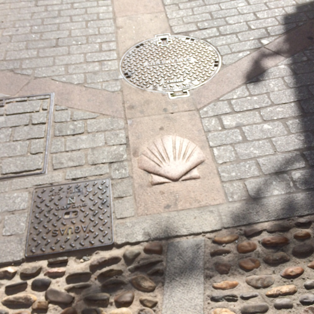 These shell symbols are common in streets and on sidewalks of cities leading to Santiago.