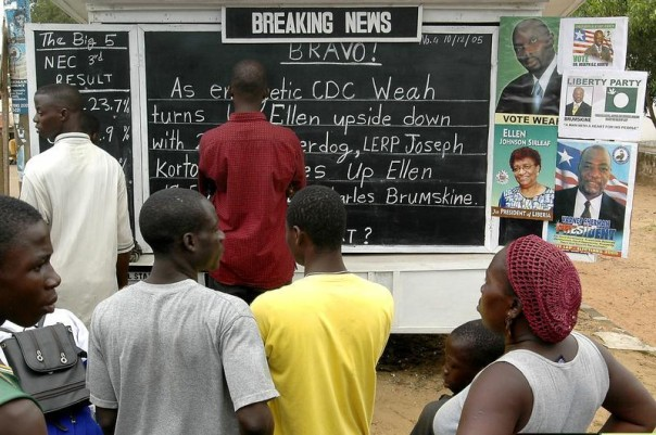Liberians pause at the Daily Talk news board to read election results updates in the Sinkor neighborhood of Monrovia, Liberia, in 2005. REUTERS/Stringer