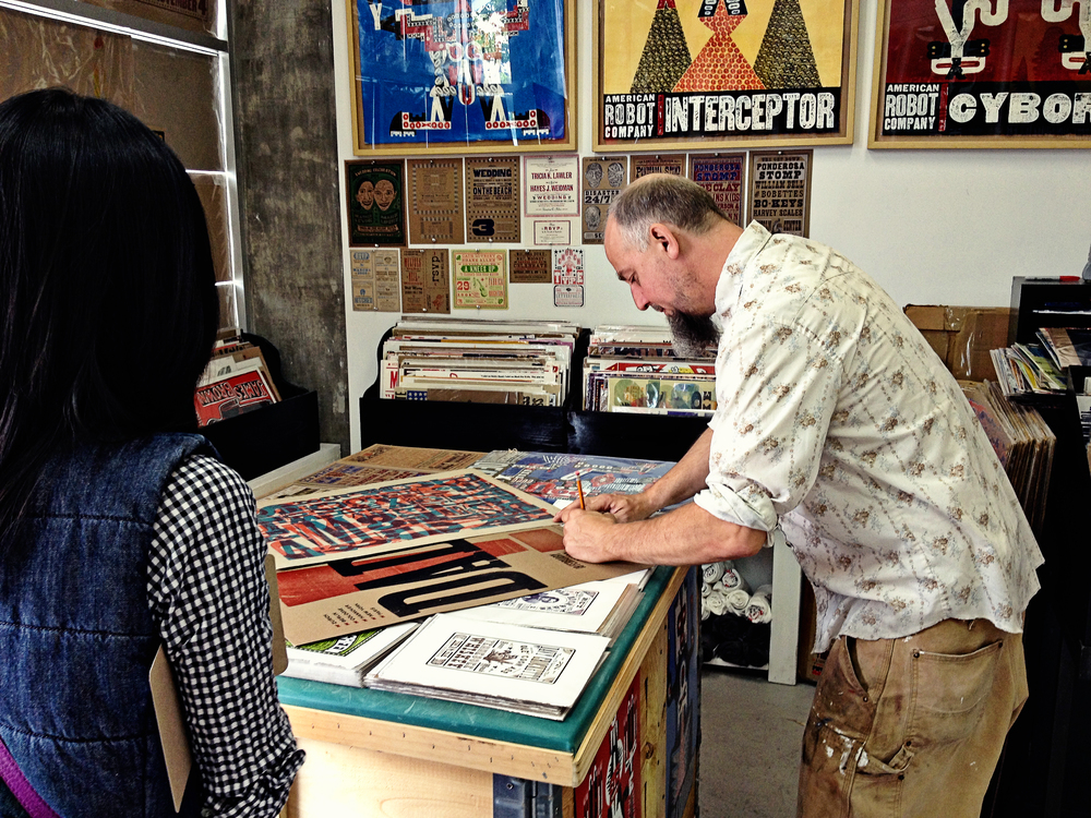 Kevin signing prints