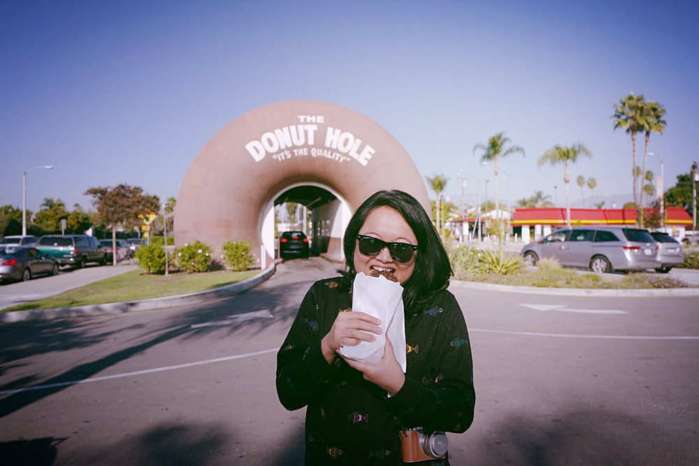 Biting into a chocolate chip-covered donut from The Donut Hole in La Puente, California.