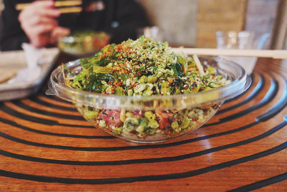 A signature Sweetfin spicy tuna poké bowl with a bamboo rice base and overflowing with a variety of toppings.