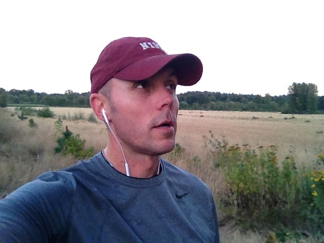 Me on a typical run. Earbuds in and a well-worn Nike hat.